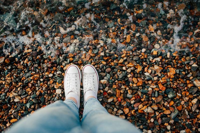 Slender legs in blue jeans and white stylish sneakers on rocky beach and wave rolls over your feet.
