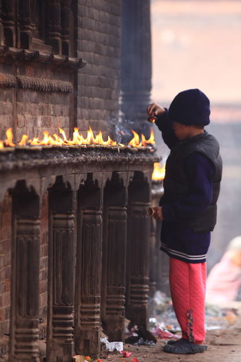 Side view of boy igniting candle at temple