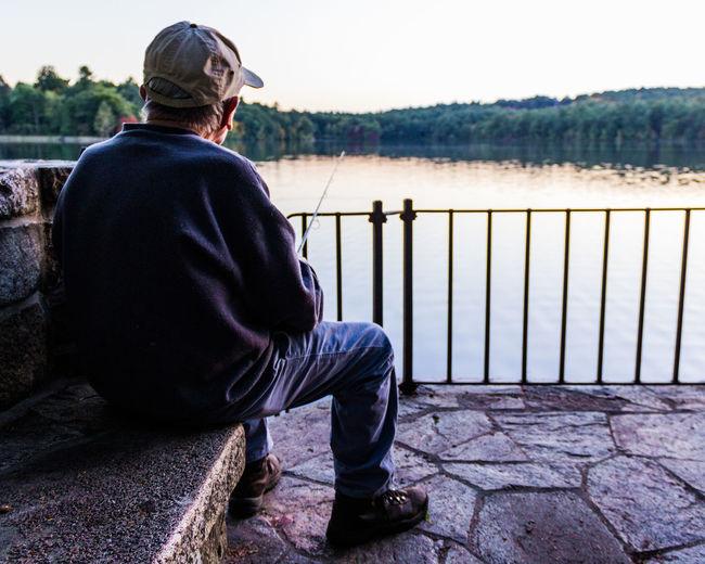 Rear View Of Old Man Fishing At Lake