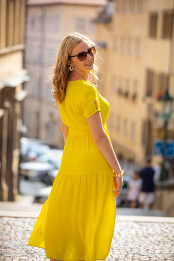 Woman in yellow dress traveling in city