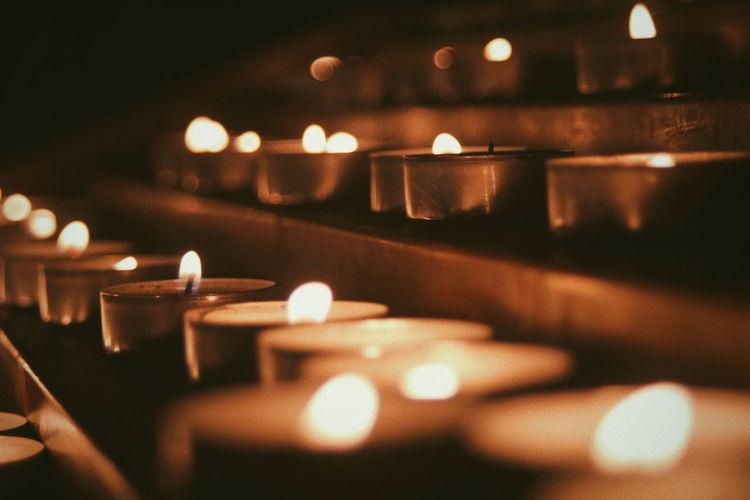 Close-up of illuminated tea light candles on altar