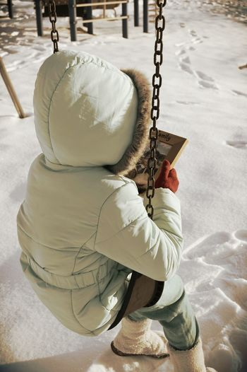 Full Length Of Child Holding Picture Frame While Sitting On Swing During Winter