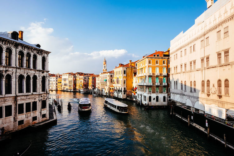 Passenger crafts sailing in grand canal amidst buildings against sky