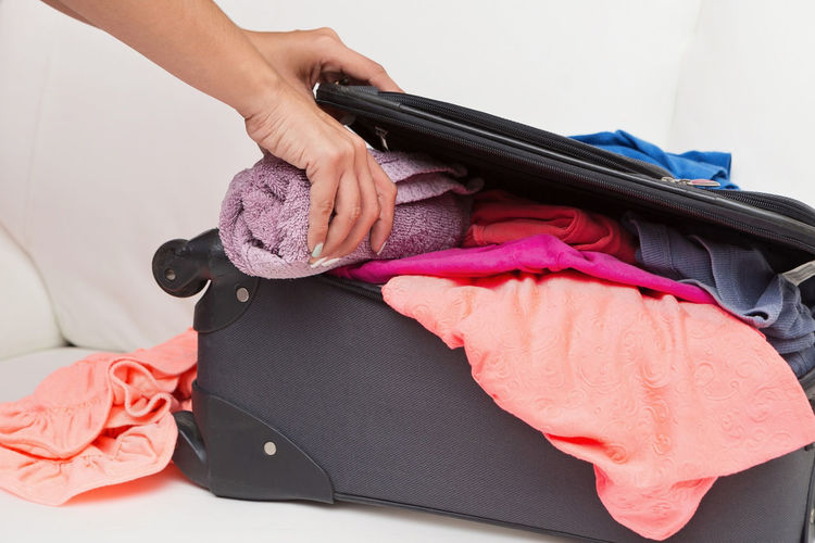 Cropped image of woman packing luggage