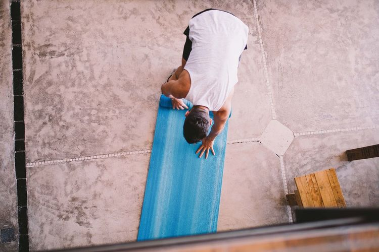 High angle view of man rolling exercise mat at yoga studio