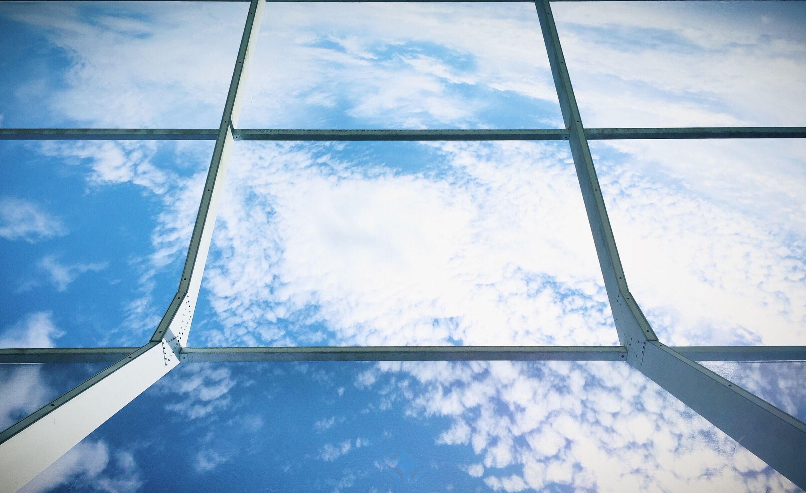 sky, low angle view, cloud - sky, cloudy, cloud, directly below, day, glass - material, blue, cloudscape, weather, no people, built structure, nature, window, part of, outdoors, backgrounds, overcast, full frame