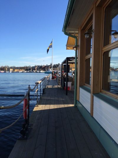 People at coffee shop by swedish flag on lake