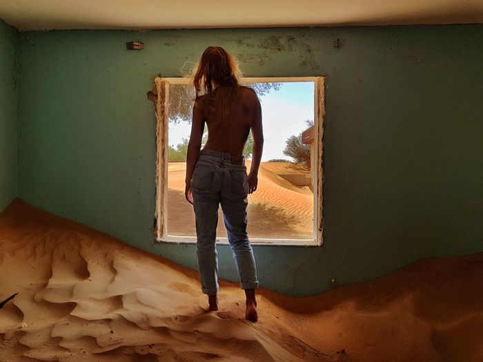 Abandoned house Window Lonely Desert Abandoned House Sitting Alone Full Length One Person Real People Rear View Casual Clothing Lifestyles Standing Women