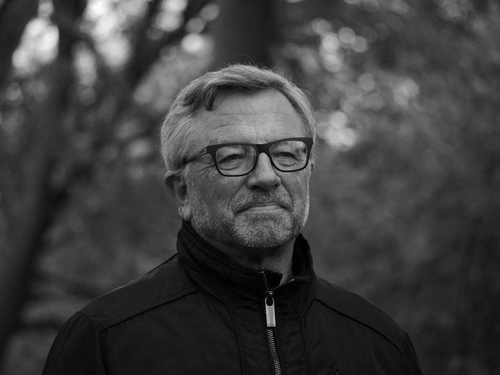 Close-up of senior man wearing eyeglasses against trees