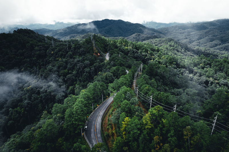 High angle view of road amidst trees against sky
