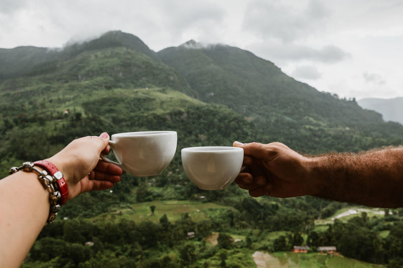 Sri Lanka Beauty In Nature Body Part Cup Day Drink Finger Food And Drink Hand Holding Hot Drink Human Body Part Human Hand Human Limb Leisure Activity Lifestyles Mountain Mountain Range Mug Nature Nuwara Eliya Outdoors People Real People Refreshment Tea Cup Travel Destinations Travelers
