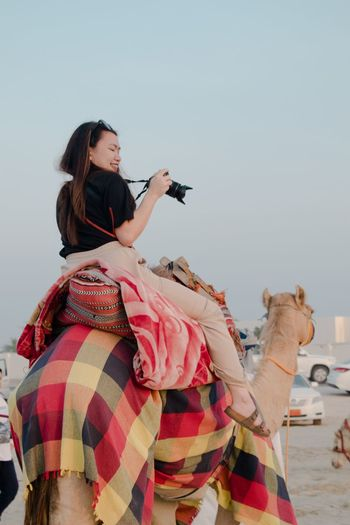Ancient means of transportation. Woman riding Camel Journey Travel Transportation Women Lifestyles One Person Young Adult Young Women Real People It's About The Journey Side View Sky Leisure Activity Vertebrate Adult Holding Hair Clothing Clear Sky Copy Space Nature Hairstyle It's About The Journey It's About The Journey Moments Of Happiness