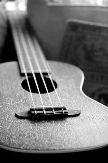 An ukulele is lying on a couch. Close Up Close-up Fretboard Guitar Indoors  Music Musical Equipment Musical Instrument Musical Instrument String No People Ukulele Woodwind Instrument