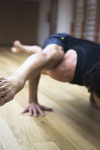 Low section of man relaxing on wooden floor