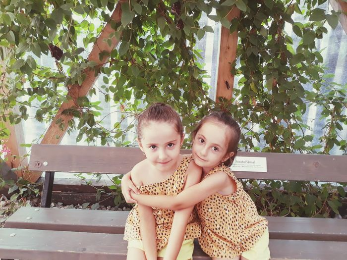 Portrait of siblings sitting outdoors