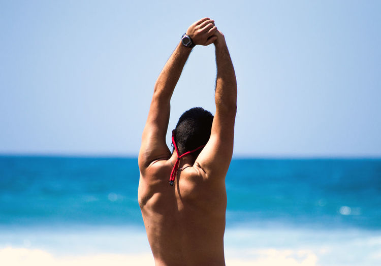 Rear View Of Shirtless Man Standing At Beach Against Clear Sky