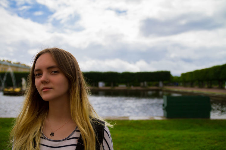 Portrait of young woman against river