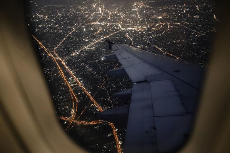Illuminated cityscape seen through airplane window
