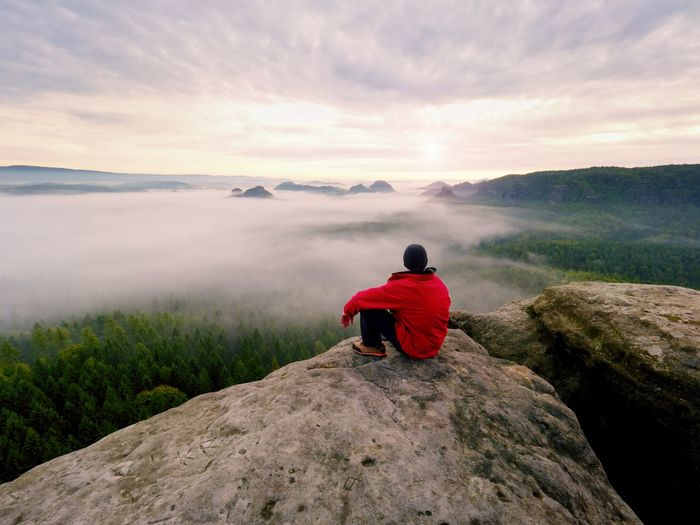 Enjoy life. man in black trousers, jacket and dark cap sit on cliff's edge and looking to mist
