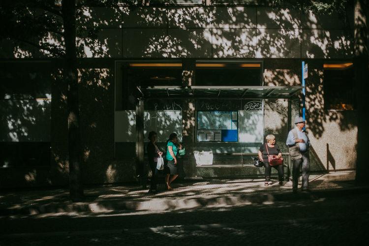 Group Of People Lifestyles Men Walking Adult Women Bus Stop Sunlight Shadow Life
