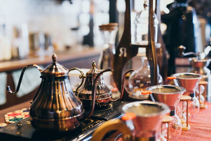 Close-Up Of Teapots With Coffee Makers On Table