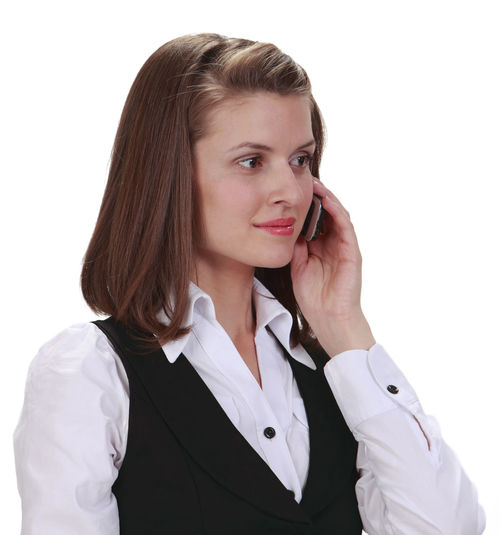 Side view of a young woman on the phone against a white background. White Background One Person Portrait Studio Shot Cut Out Young Adult Using Phone Adult Telephone Females Wireless Technology Communication Talking Mobile Phone Call Phone Call Businesswoman Business Person Young Woman Isolated White Background