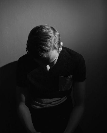 Sad man sitting against wall