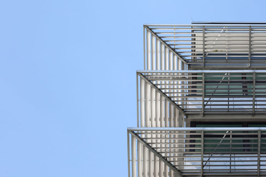 Low angle view of modern office building facade Balustrade City Clear Sky Copy Space Modern Abstract Architectural Feature Architecture Blinds Blue Building Exterior Building Feature Built Structure Clear Sky Day Low Angle View Metal Metallic Office Building Exterior Outdoors Pattern Railing Repetition Sky Steps