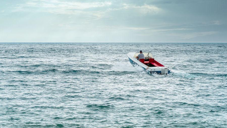 Forward - beyond the horizon in motorboat on sea against sky