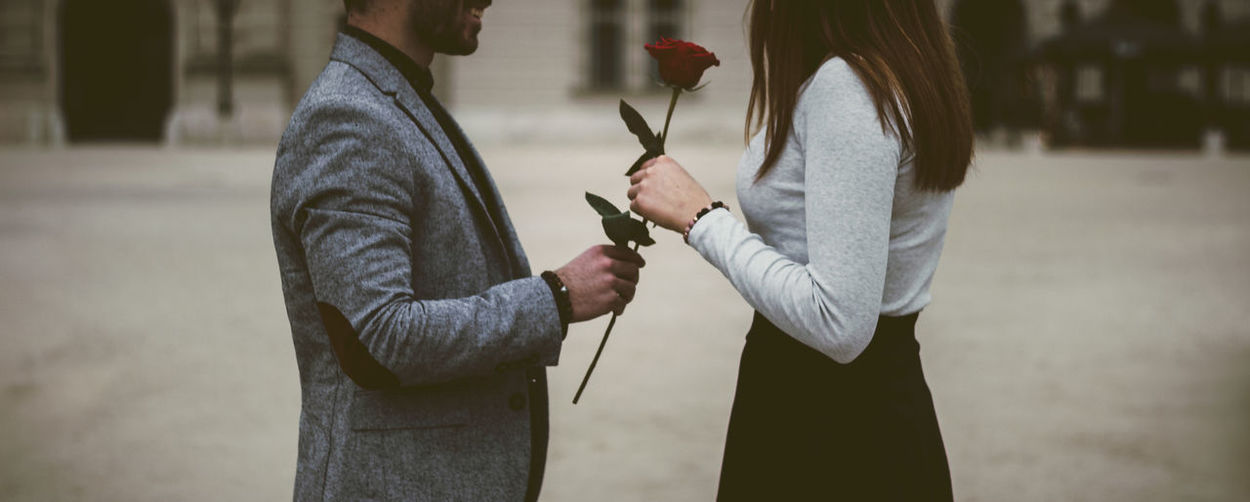 man giving a rose to young woman Standing Holding Focus On Foreground Two People Men Hand Casual Clothing People Real People Midsection Side View Adult Lifestyles Day Human Hand Three Quarter Length Waist Up Clothing Women Couple - Relationship Rose - Flower Red Present Valentine Valentine's Day