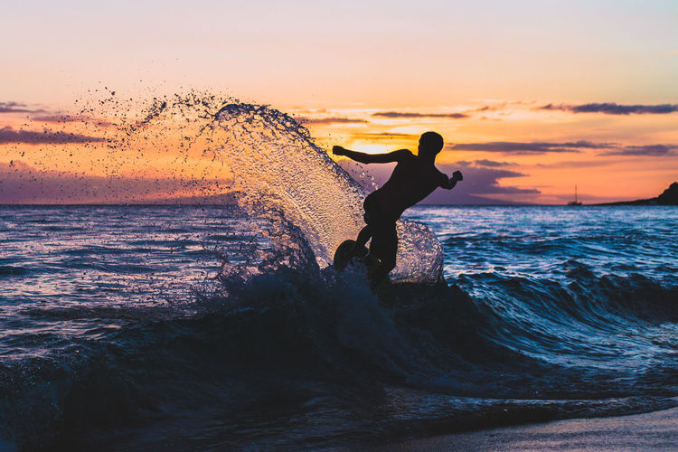 Man Surfing In Sea Against Sky During Sunset