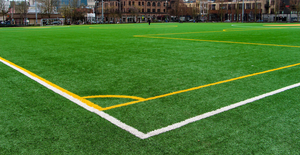 Soccer field and buildings in city