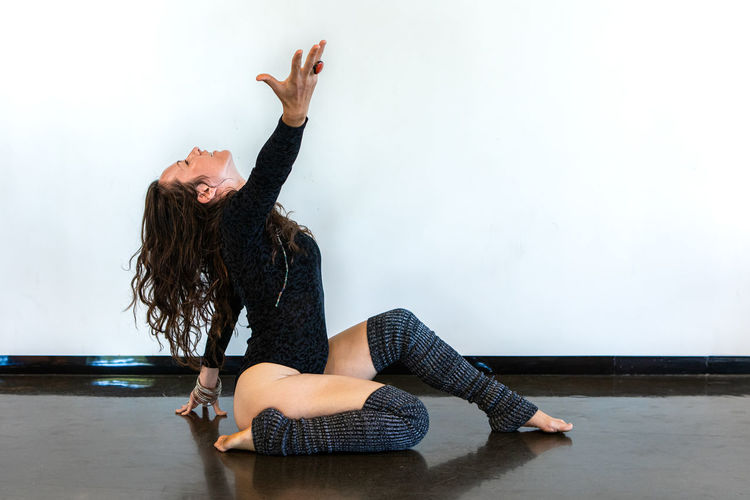 Full length of woman with hand raised dancing against wall