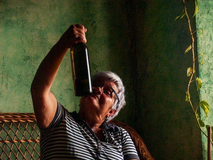 Drunk woman looking at wine bottle at home