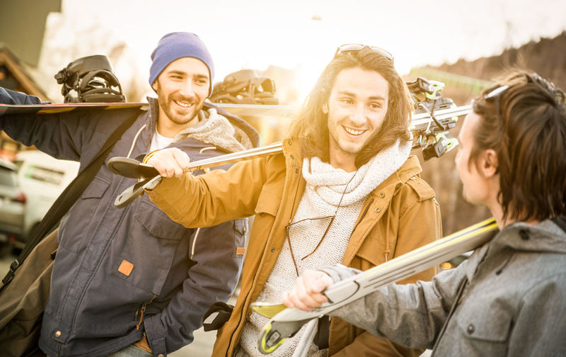 Friends Holding Ski Equipment While Standing Outdoors