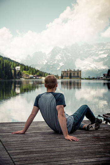 Rear view of man sitting on pier over lake against sky