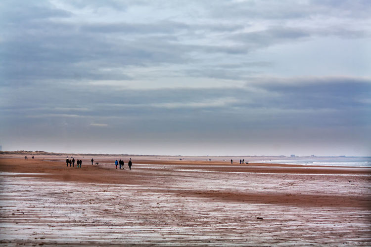 People at snowy beach against cloudy sky