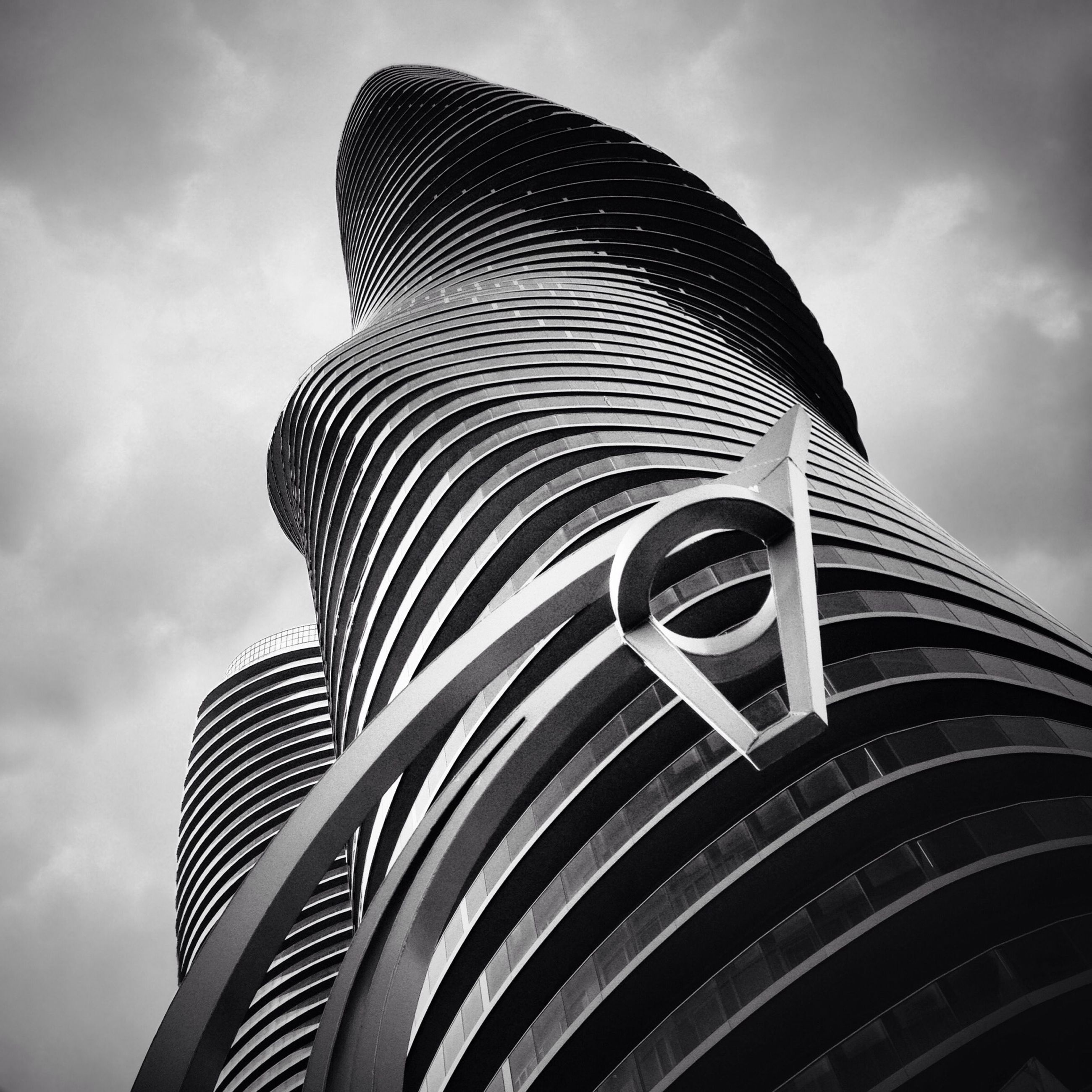 low angle view, sky, cloud - sky, architecture, built structure, building exterior, cloudy, cloud, no people, outdoors, modern, day, pattern, architectural feature, design, city, arts culture and entertainment, famous place, tall - high, metal