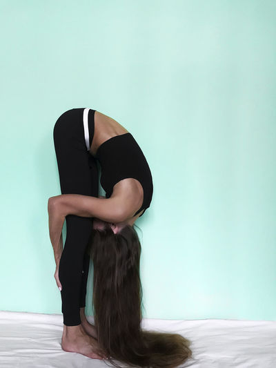 Side view of woman stretching on bed against turquoise wall