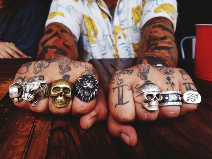 Midsection Of Hipster Tattooed Man Wearing Various Finger Rings