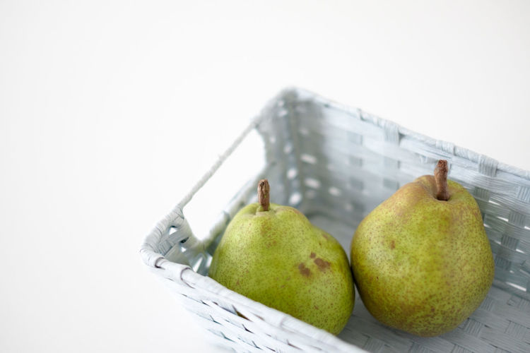 Two pears in a light blue basket Food Still Life Fruit Food And Drink Indoors  Basket Pear Freshness Close-up White Background Ripe Healthy Eating No People Wellbeing Green Color Studio Shot Copy Space Group Of Objects Apple - Fruit Hatamoto Shinichi