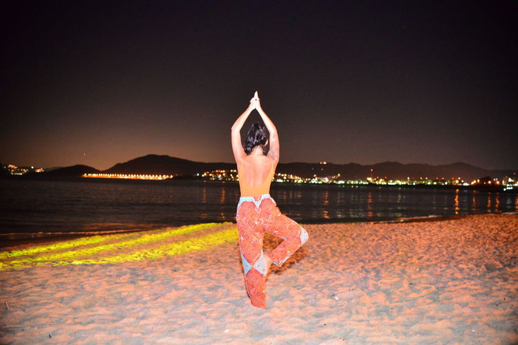 Rear View Of Mid Adult Woman Exercising At Beach Against Sky During Night