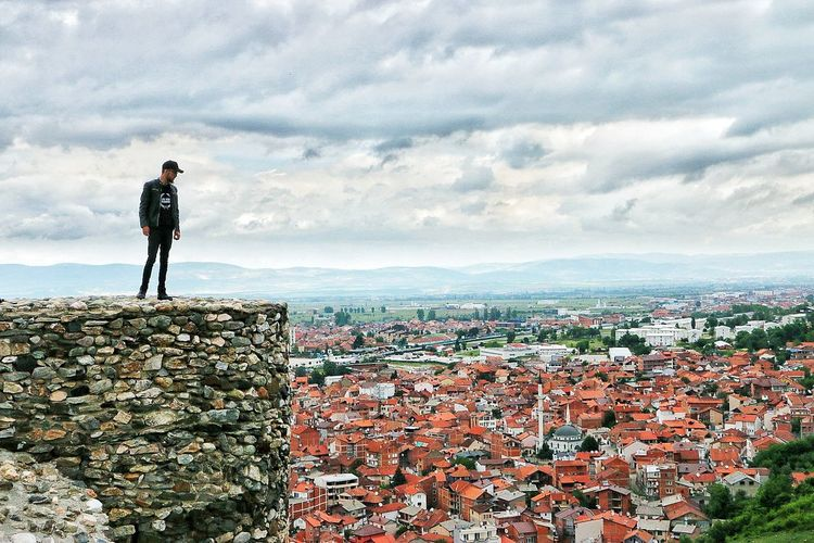 Man Standing On Wall Over Townscape Against Sky
