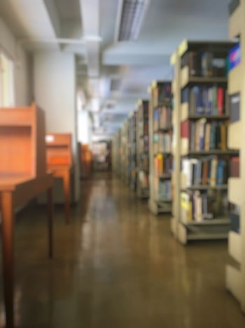 Blurred background of library in University space between brown desk near the window and book shelf Indoors  Book Education Bookshelf In A Row Library No People Knowledge Space Walk Queit Study Learn Fool  Journal Professional Improvement