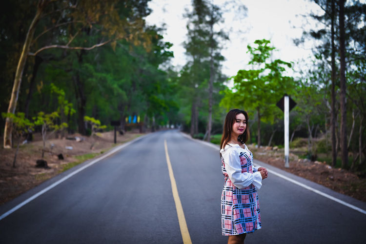 Full length of woman on road against trees