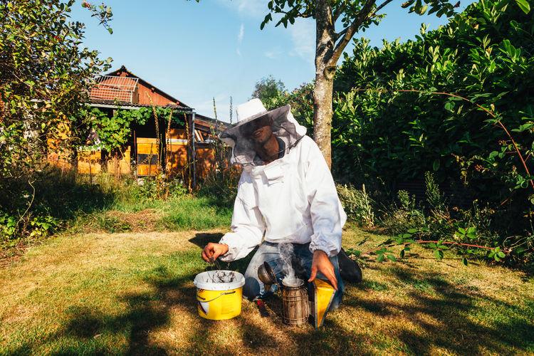 Beekeeper kneeling by equipment on grass