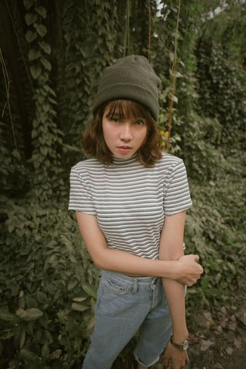 Full length of girl wearing hat standing in forest
