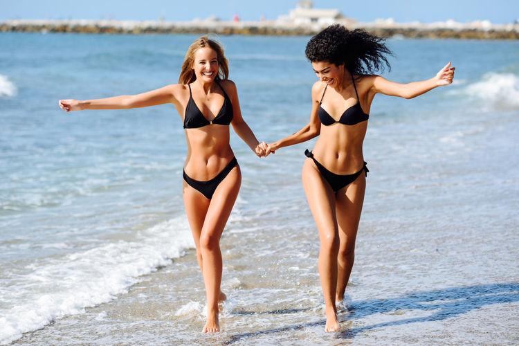 Happy friends walking at beach