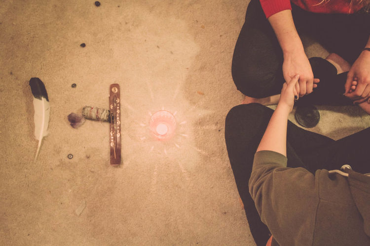 Low section man and woman by tea light candle on rug during wiccan ceremony