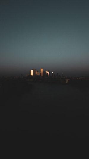 City buildings against clear sky at dusk
